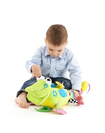 developmental: Baby boy busy playing with colorful developmental soft toy. Stock Photo