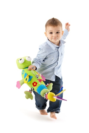 soft toy: Cute baby boy running with colorful soft toy handheld, cutout on white. Stock Photo