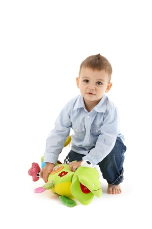 Sweet toddler boy playing with colorful soft toy, smiling, looking at camera. photo