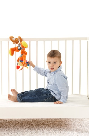 Happy little kid sitting in babys cot, playing with developmental soft toy. photo