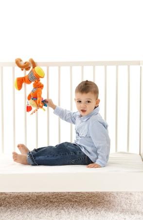 developmental: Happy little kid sitting in babys cot, playing with developmental soft toy.