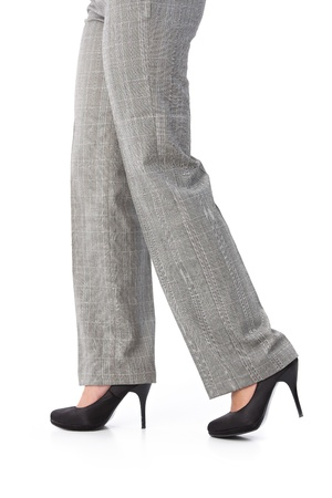 Female legs walking in trousers and high heel shoes. photo