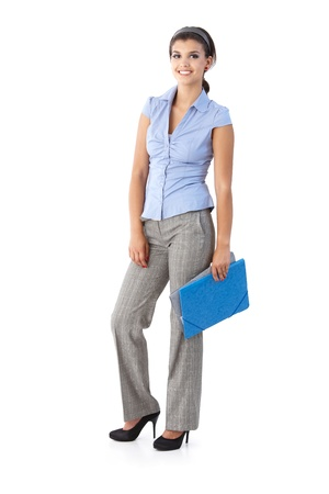 Happy young woman holding folders, looking at camera.