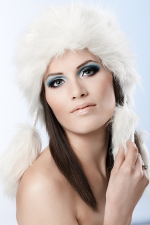 Beauty portrait of attractive young woman wearing white fur cap, looking at camera. photo