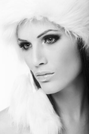 Beauty portrait of attractive young woman wearing white fur cap, looking away. Black and white photo. photo
