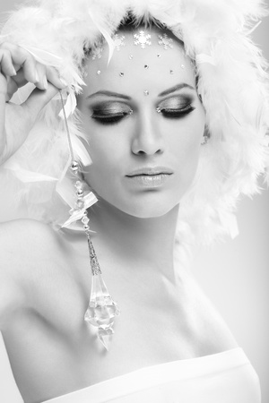 Conceptual beauty portrait of young woman in winter makeup wearing white feather cap. photo