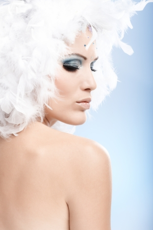 Conceptual beauty portrait of young woman in winter makeup wearing white feather cap. Stock Photo - 11843594