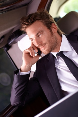Elegant businessman sitting in luxury car, talking on mobile phone. photo