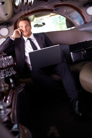 Handsome young businessman sitting in limousine, talking on mobile phone, using laptop computer. Stock Photo