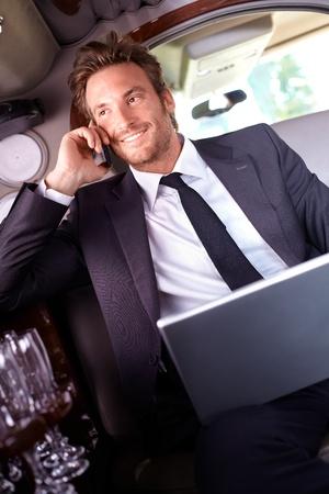 hombre sentado: Joven hombre de negocios feliz sentado en la limosina, hablando por m�vil, usando la computadora port�til.