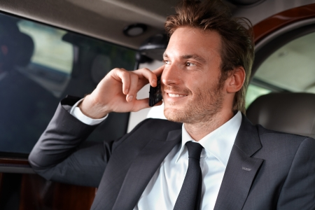 elegance: Elegant businessman traveling in luxury car, talking on mobile phone, smiling.