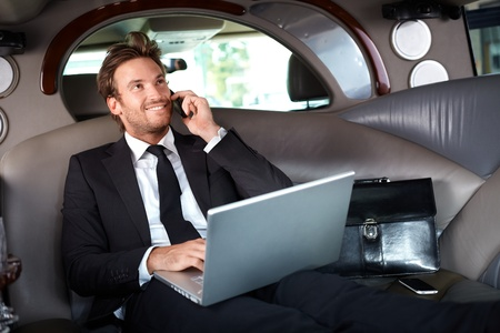 calling on phone: Smiling handsome businessman sitting in luxury limousine, working on laptop computer, smiling. Stock Photo