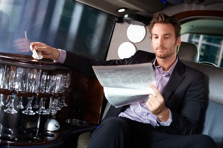 offish: Handsome young man sitting in limousine, reading newspaper.