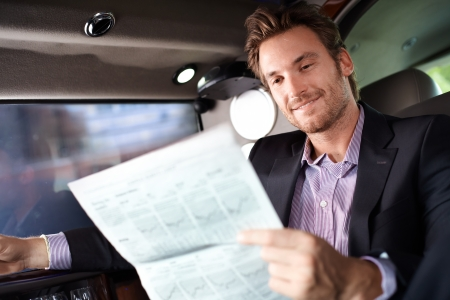 Happy young man reading newspaper in luxury car, smiling. photo