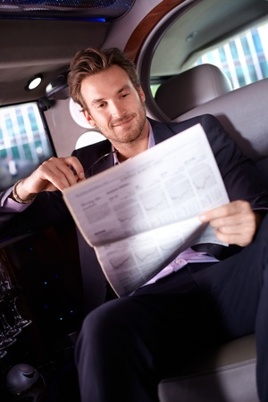 Smart young man reading newspaper in limousine, smiling. photo