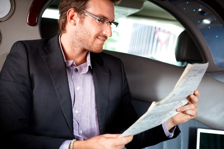 Elegant young man reading newspaper in luxury car. photo