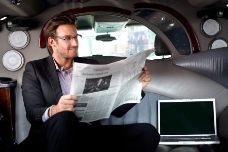 Handsome junge Geschäftsmann sitzt in der Limousine, liest Zeitung, lächelnd.