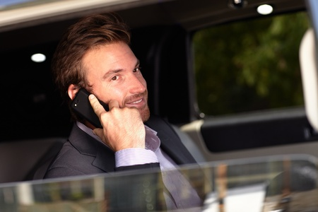 Handsome young businessman on phone call, sitting in elegant car. photo