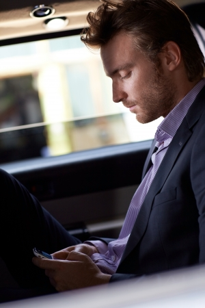 Smart man texting on cellphone, sitting in elegant car. photo