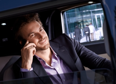 Elegant man on phone call in luxury automobile, smiling. photo