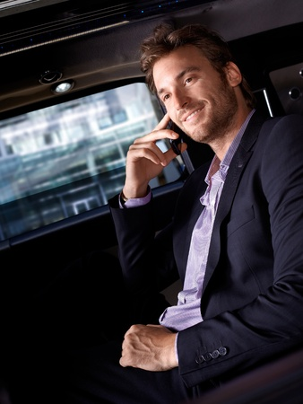 Smiling businessman sitting in luxury car, talking on mobile phone. photo