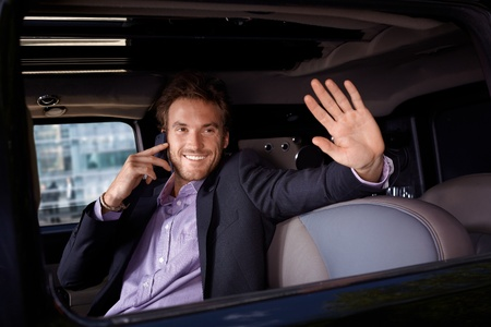 Celebrity talking on mobile, waving from limousine window, smiling. photo