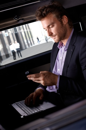 Smart young businessman using laptop and mobile in luxury automobile, working. Stock Photo