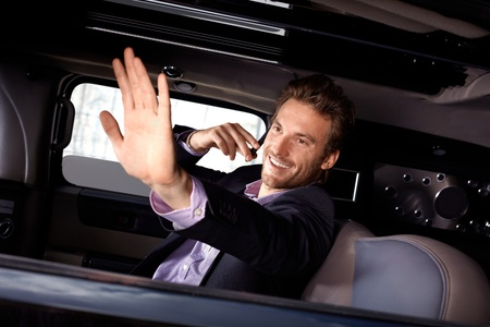 Young celebrity waving from limousine, talking on mobile phone, smiling. photo