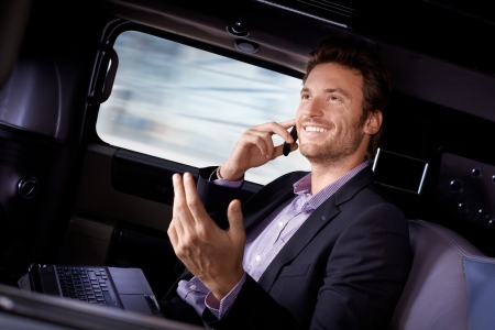 Handsome young businessman traveling in limousine, working on laptop computer, talking on mobile phone, smiling. photo