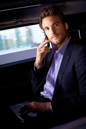 offish: Handsome young man sitting in limousine, working on laptop computer, talking on mobile.