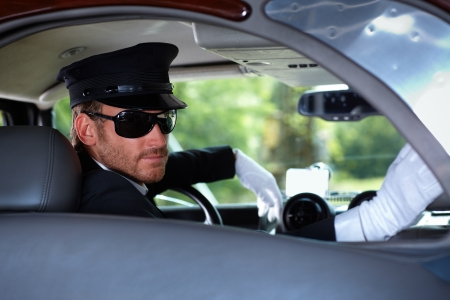 chauffeur: Young chauffeur in elegant automobile. Stock Photo