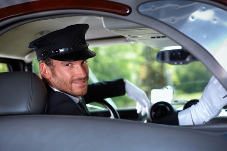 Handsome young chauffeur in limousine, smiling. photo