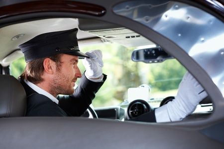 chauffeur: Elegant chauffeur sitting in luxurious car.