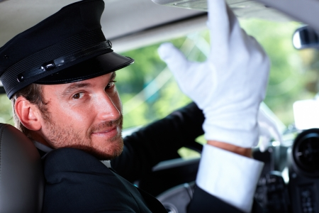 Handsome young chauffeur in elegant car, smiling. Stock Photo - 12063362
