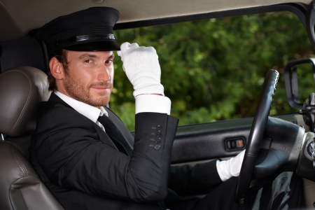 Confident chauffeur sitting in elegant automobile. Stock Photo