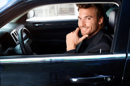 Smiling handsome man sitting in limousine. Stock Photo