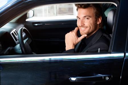 hombre sentado: Sonriente hombre guapo sentado en limusina.
