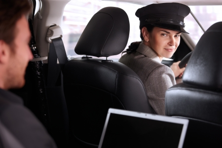 chauffeur: Pretty female chauffeur smiling in luxury car, businessman working on back seat. Stock Photo