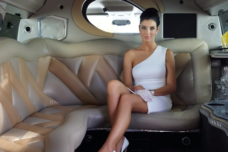 Beautiful elegant woman sitting in luxury limousine. photo