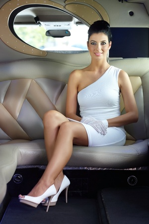 elegance: Elegant luxury woman sitting in limousine, smiling. Stock Photo