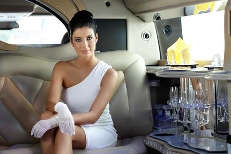 Beautiful smart woman sitting in limousine. photo