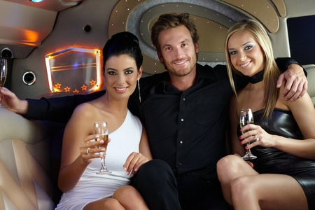 fancy dress: Happy elegant young people in luxury limousine, drinking champagne, having fun. Stock Photo