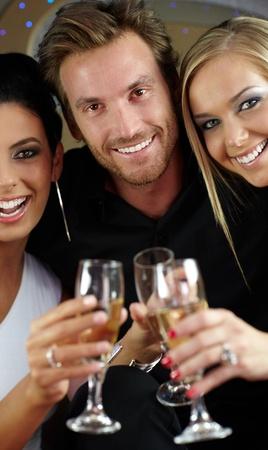 clinking: Hermosas j�venes bebiendo champ�n, vasos tintineando, sonriendo feliz.
