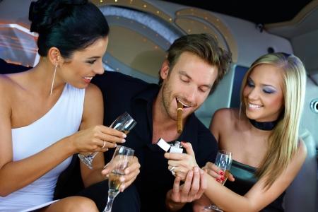 smoking girl: Upper ten having fun in luxury car, drinking champagne, smoking cigar. Stock Photo