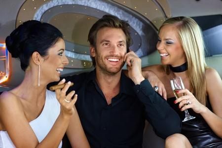 cigars: Happy young people having fun in luxury car, drinking, smoking cigar.