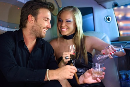 limo: Attractive young couple having fun in limousine, drinking. Stock Photo