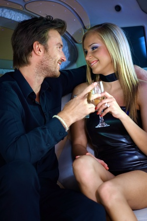 limousine: Attractive young couple having fun in luxury car.