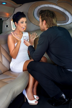 Young man proposing beautiful woman in limousine with engagement ring. photo