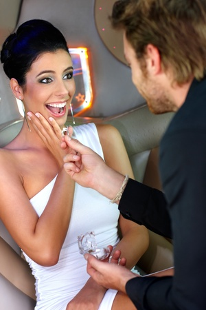 Young man engaging surprised beautiful woman with engagement ring. Stock Photo - 12063310