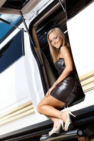 Sexy blond wearing leather outfit, smiling in limousine door. photo
